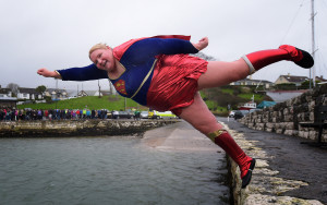 Angela McClements takes the plunge as swimmers brave the icy waters during the New Year's Day swim at Carnlough harbour on January 1, 2015 in Carnlough, Northern Ireland. The annual event on the north Antrim coast supports Spina Bifida and Hydrocephalus charities. (Photo by Charles McQuillan/Getty Images)